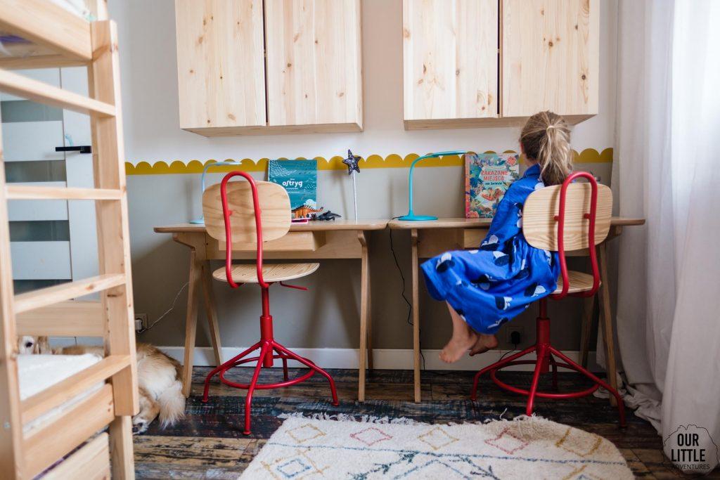 Dziewczynka siedzi przy biurku w pokoju, w tle widać książki Zakazane miejsce na świecie i Milion ostryg - książki obrazkowe dla dzieci Znak Emotikon, zdjęcie autorstwa OurLittleAdventures.pl