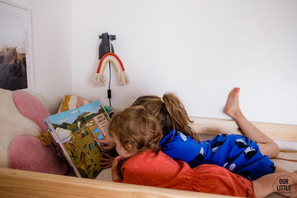 Dziewczynki czytające książkę Zakazane miejsce na świecie - książki obrazkowe dla dzieci Znak Emotikon, zdjęcie autorstwa OurLittleAdventures.pl