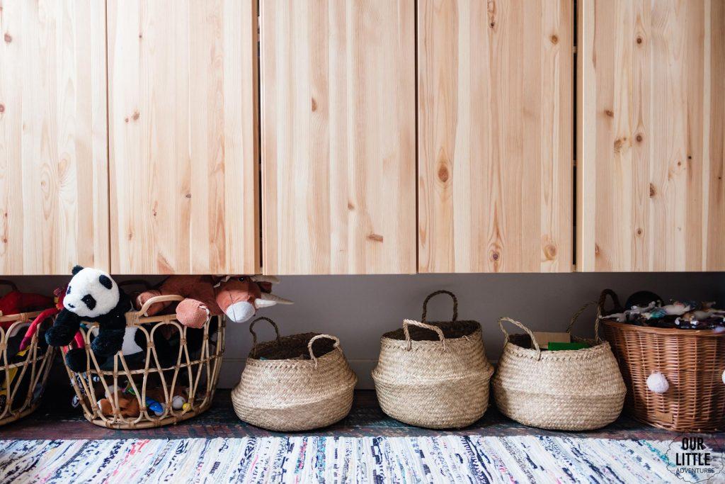 Kosze z zabawkami stojące pod szafkami drewnianymi, Pokój dla rodzeństwa - fot. OurLittleAdventures.pl
