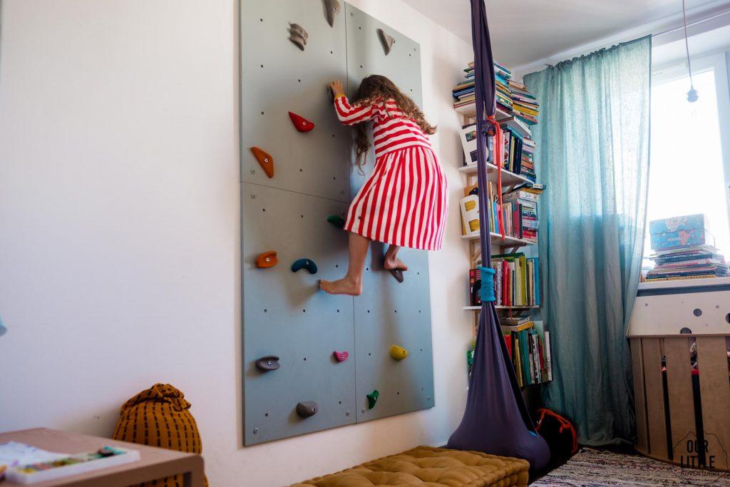 Dziewczynka w sukience w paski wchodzi na ściankę wspinaczkową. Pokój dla rodzeństwa - fot. OurLittleAdventures.pl