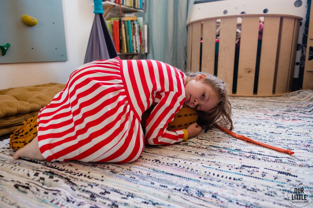 Dziewczynka w sukience w paski leży na pufie sensorycznej, Pokój dla rodzeństwa - fot. OurLittleAdventures.pl