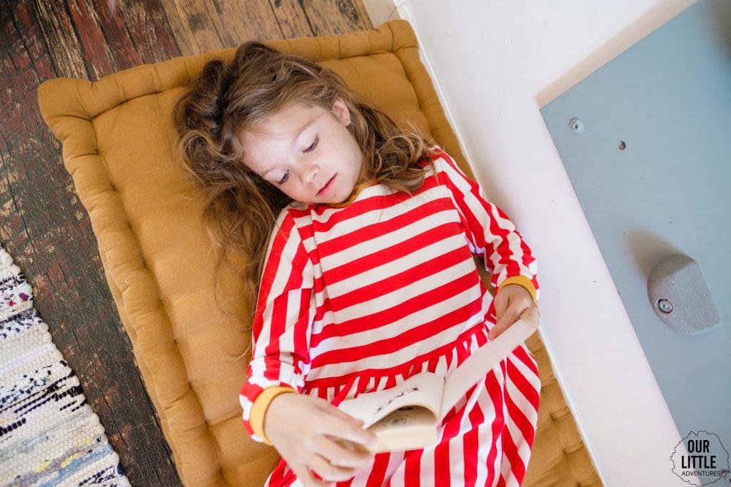 Dziewczynka w sukience w paski czyta książkę i leży na materacu, Pokój dla rodzeństwa - fot. OurLittleAdventures.pl