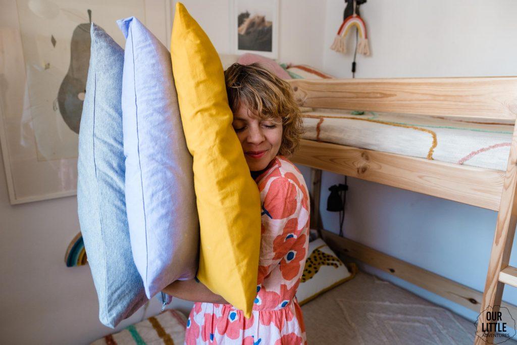 Kobieta przytula się do poduszek, fot. OurLittleAdventures.pl