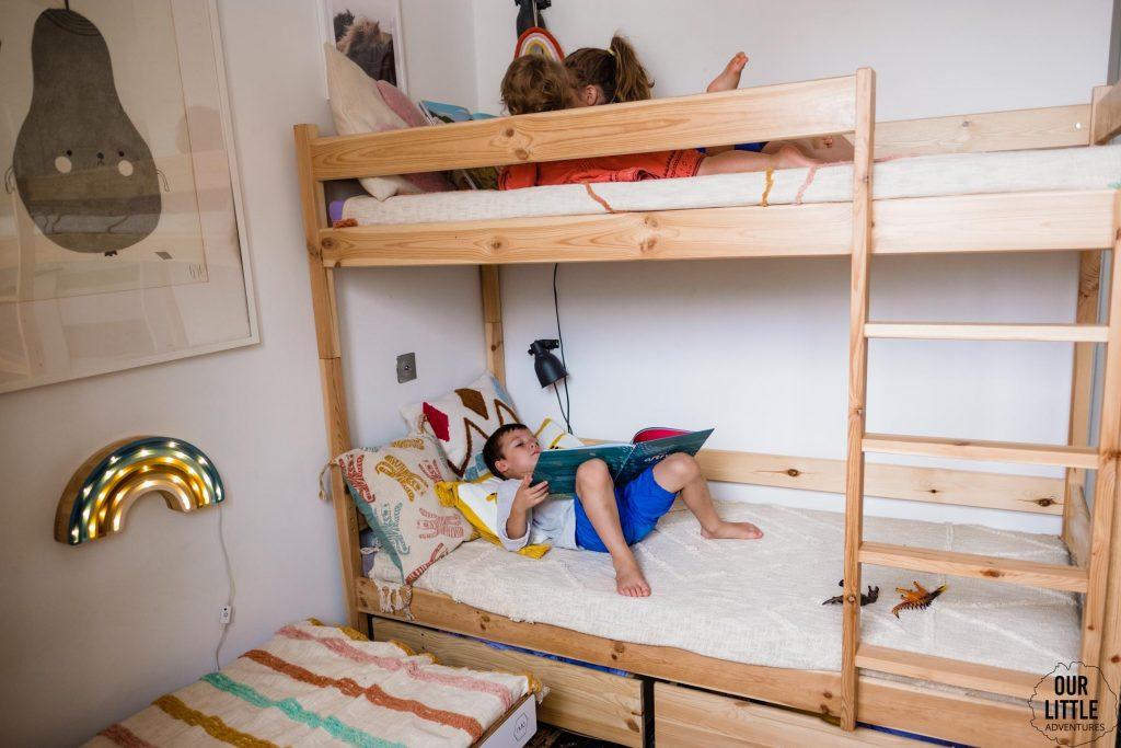 Dzieci leżą na łóżkach i czytają książki, fot. OurLittleAdventures.pl