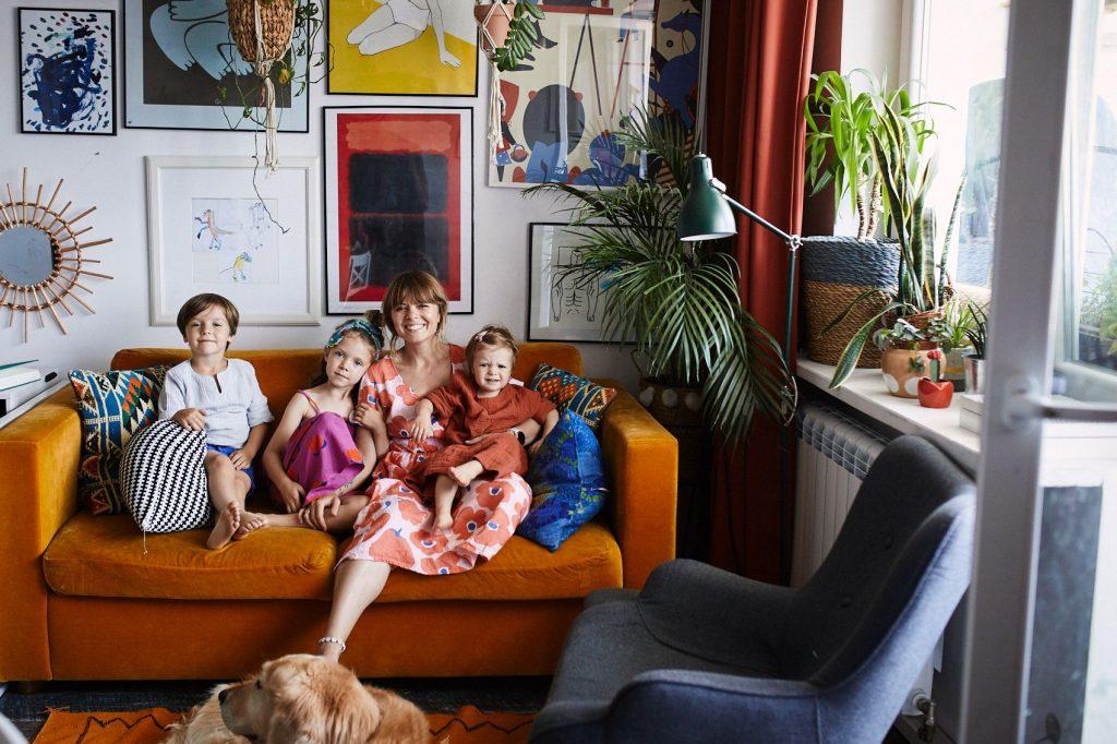 Mama z trójką dzieci siedzi na kanapie, pies leży na podłodze, fot. Observatorium