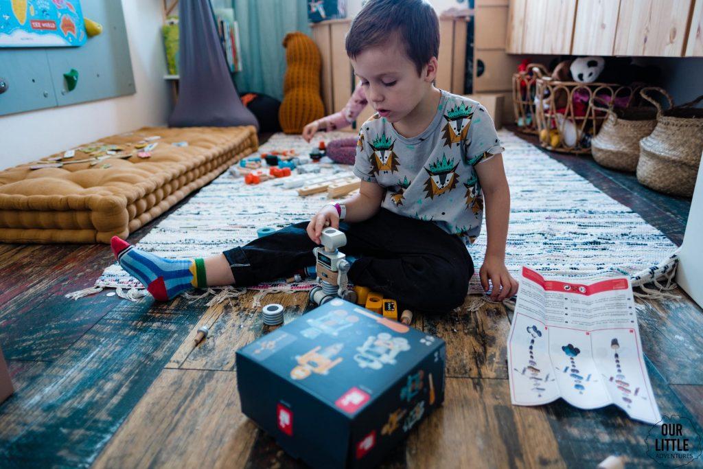 Chłopiec siedzi na podłodze w bawialni i układa klocki Janod, zdjęcie autorstwa Ourlittleadventures.pl