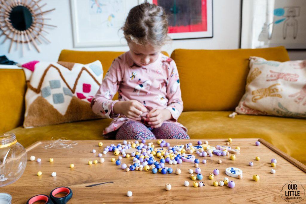 Dziewczynka nawleka koraliki na nitkę, zdjęcie autorstwa Ourlittleadventures.pl