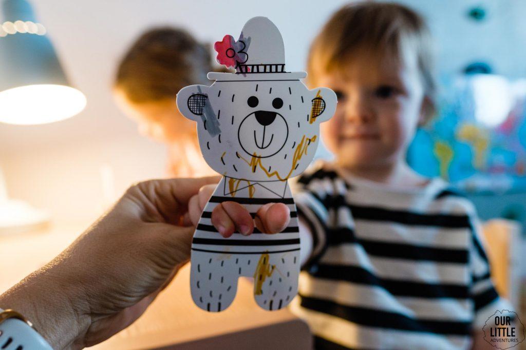 Dziewczynka trzyma w rączkach papierowego misia marionetkę, zdjęcie autorstwa Ourlittleadventures.pl