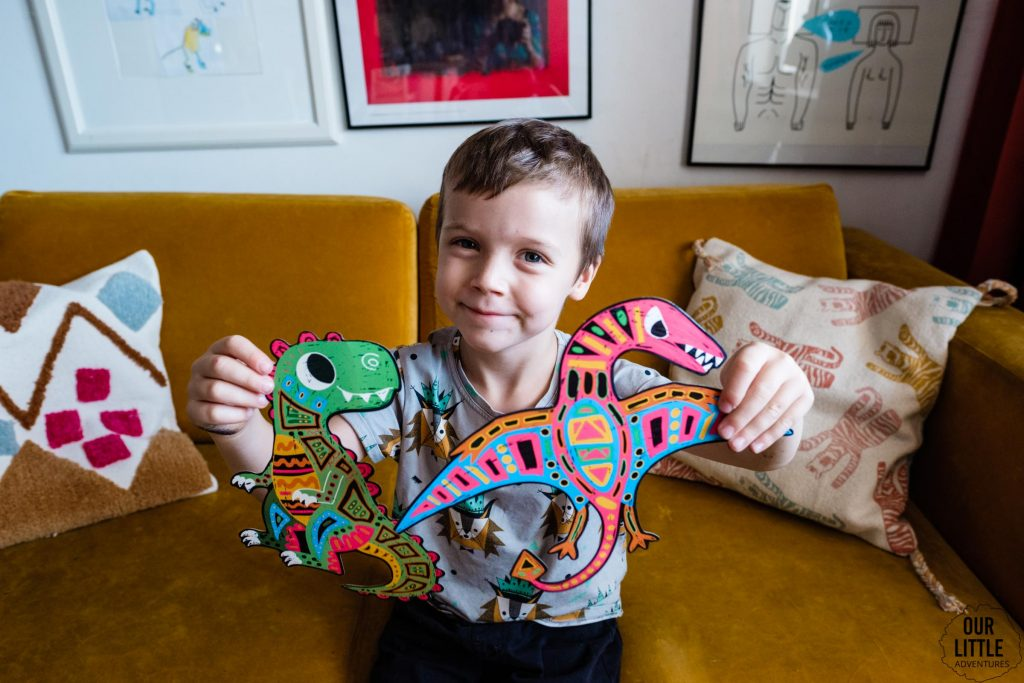 Chłopiec pokazuje papierowe dinozaury, zdjęcie autorstwa Ourlittleadventures.pl
