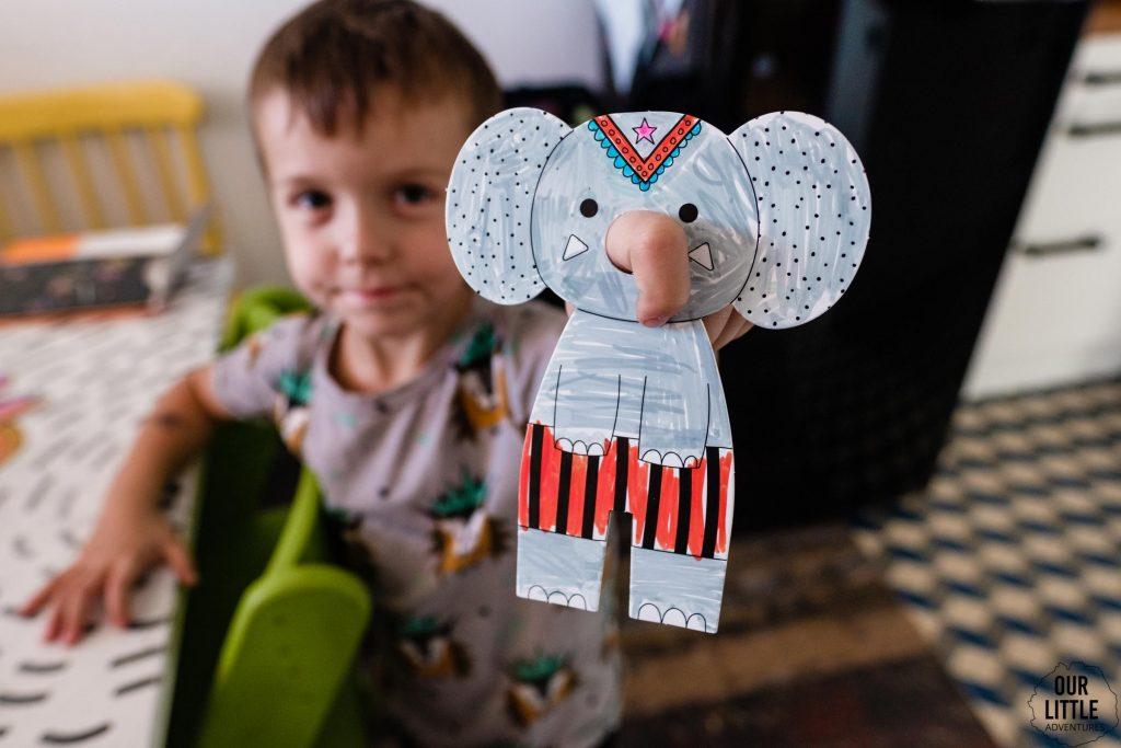 Chłopiec trzyma papierową marionetkę słonia na palcu, zdjęcie autorstwa Ourlittleadventures.pl