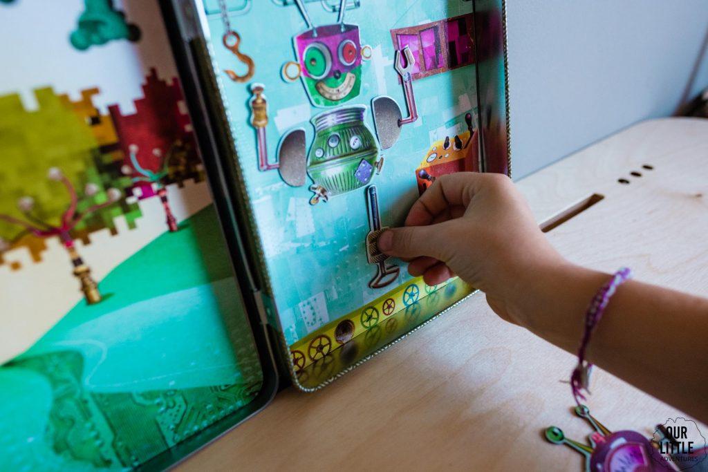 Dziewczynka układa magnetyczne roboty w układance,  zdjęcie autorstwa OurLittleAdventures.pl